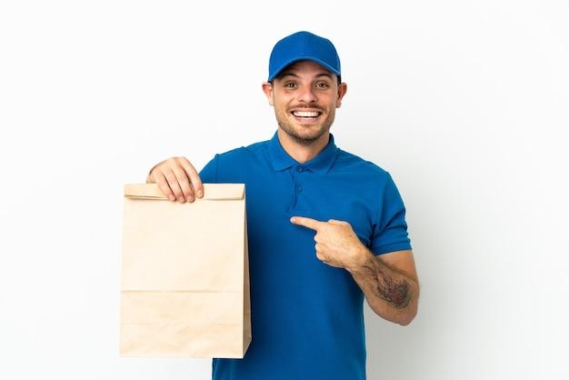 Бразилец берет сумку еды на вынос, изолированную на белом фоне с удивленным выражением лица