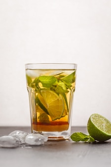 Brazilian traditional caipirinha with lime, sugar and mint. white background, dark table, copy space.