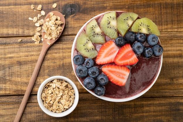 Типичная бразильская чаша асаи с фруктами и мюсли над деревянным столом.