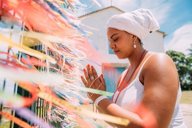 기도하는 움 반다 종교의 전통적인 바이아 의상을 입은 브라질 여성
