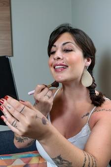 Бразильская женщина улыбается, делает татуировку и наносит макияж с помощью планшета.