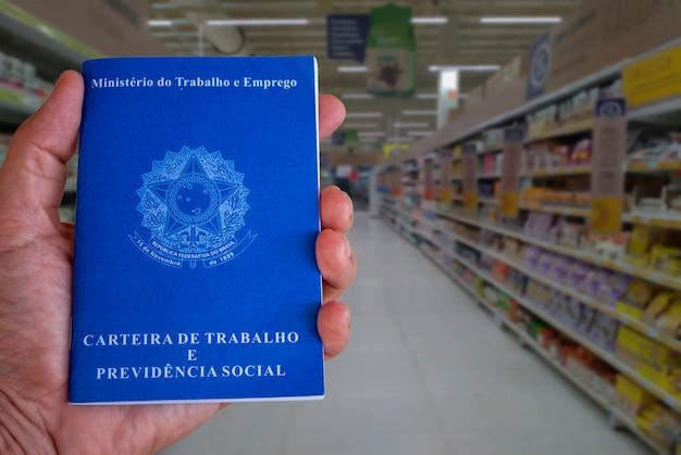 슈퍼마켓 통로의 배경이 흐릿한 브라질 작업 카드. 일과 상업의 개념