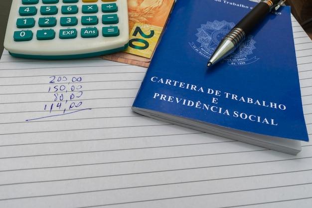 계산기, 펜, 숫자가 있는 종이가 있는 브라질 작업 카드. 재정 관리 개념입니다.