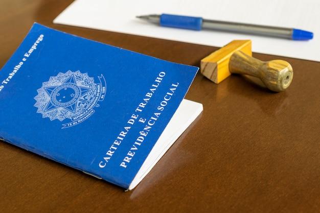 テーブルにスタンプ、ペン、紙が付いたブラジルのワークカード。雇用契約の概念。
