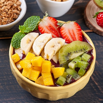 Brazilian yoghurt­ in a bowl accompanied by tropical fruits