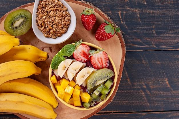 Бразильский йогурт в миске в сопровождении тропических фруктов