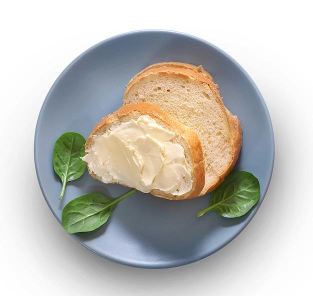 白で隔離されるプレート上のパンとバター