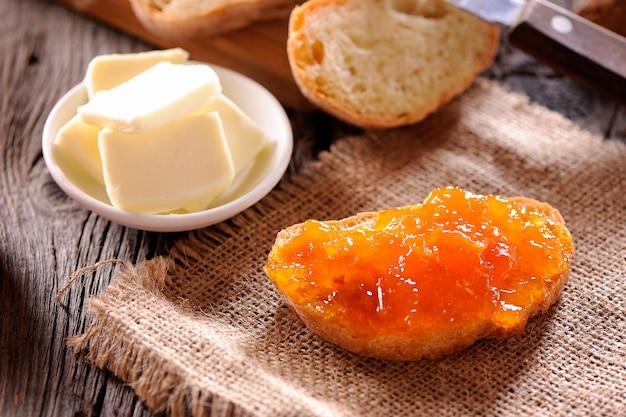 나무 테이블에 빵과 오렌지 홈메이드 잼