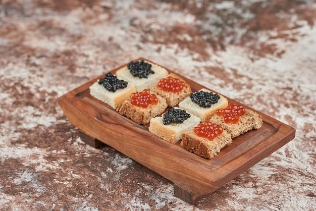 Aperitivi di pane sul marmo con caviale su tavola di legno.