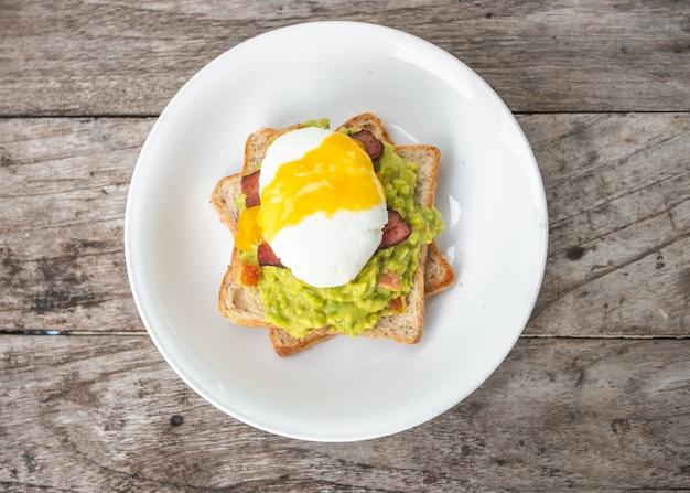 Bread, avocado sauce, bacon, spinach, egg benedict on white plate and old wood background
