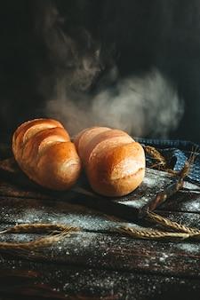 Хлеб, запеченный на деревенском столе из муки и колосья пшеницы