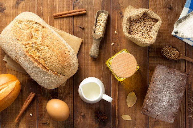 Bread and bakery ingredients on wooden table background, top view