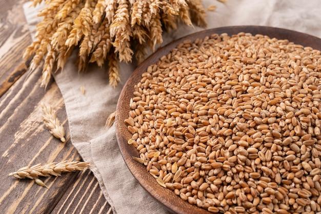 빵 굽기 배경 곡물과 귀는 소박한 나무 빵 만들기 구성에 흩어져 있습니다.
