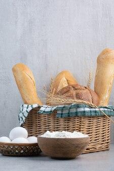 石の表面にパンかご、卵、小麦粉