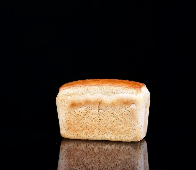 Bread on a black background with reflection