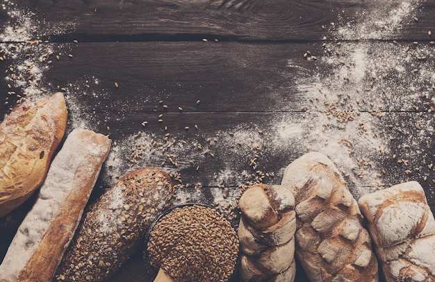 Bread border on dark wooden background. brown and white whole grain loaves still life composition with wheat flour sprinkled around. bakery, cooking and grocery store concept.