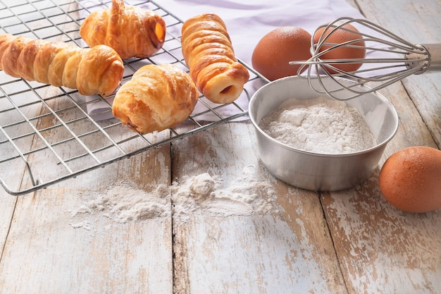 Bread  and bowl of flour on wood background