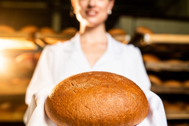 パン。パンの生産ライン。女性の手でパン。