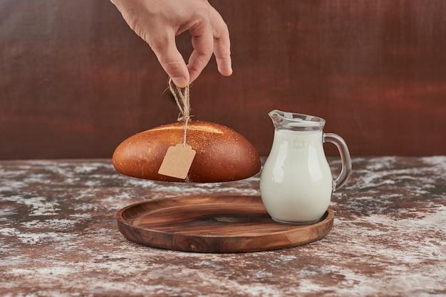 Panino di pane isolato su marmo con un barattolo di latte.