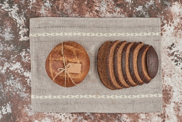 Bread bun on marble on piece of towel.