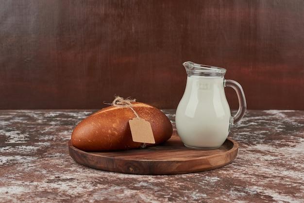 Panino di pane su marmo con etichetta e un barattolo di latte.
