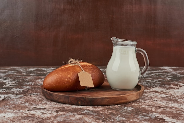 Булочка на мраморе с биркой и банкой с молоком.