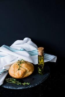 Булочка для хлеба; thymes; оливковое масло и белая салфетка на шифер на черном фоне