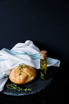 Bread bun; thymes; olive oil and white napkin on slate against black background