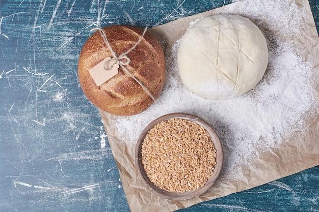 青いテーブルの上に生地と小麦のパンパン。
