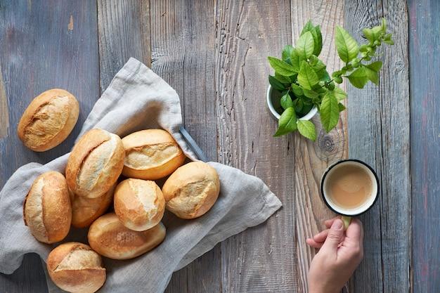 Булочки хлеба в корзине на деревенском дереве, весенние листья и рука с чашкой кофе