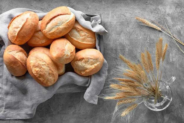 Булочки в корзине на деревенском дереве с колосьями пшеницы
