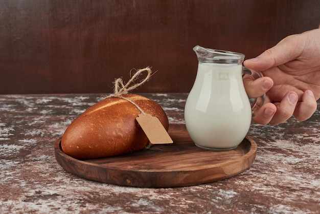 Focacce di pane su marmo con un barattolo di latte.