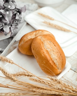 Bread buns with wheat branch on the table
