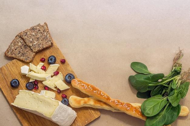 Хлеб, сыр бри с ягодами и зеленью