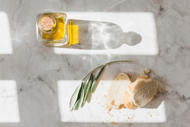 Bread and closed oil bottle on white marble