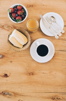 Bread; coffee cup; jam; fresh berries and cutlery on plate against wooden background