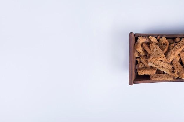 Хлебные крекеры на деревянном подносе справа.