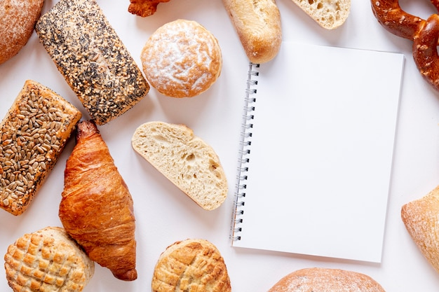 Bread and croissants near a notebook