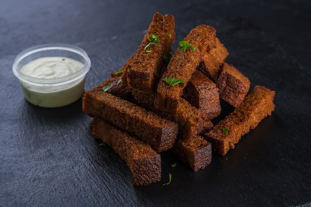 Хлебные гренки с майонезным соусом на черном подносе