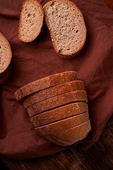Bread on dark wooden table and brown napkin. bread slices and crumbs viewed from above.