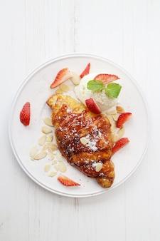 Bread for desert with vanilla cream and sliced strawberry