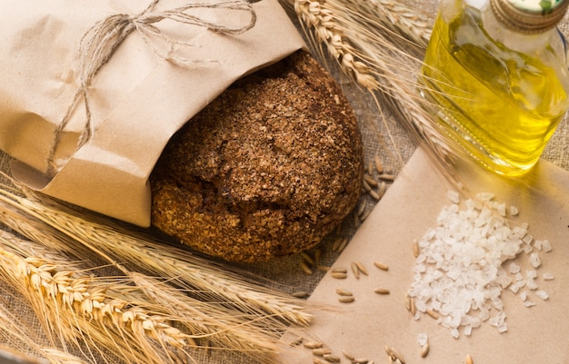 Bread, ears, grains and vegetable oil on sackcloth.