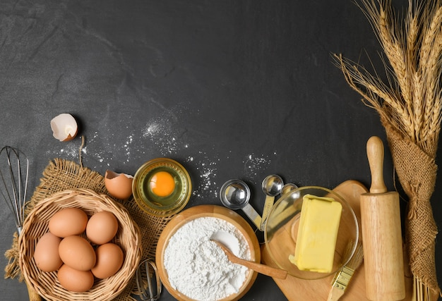 Bread flour with fresh egg, unsalted butter and accessories bakery on wood background, prepare for homemade bakery concept