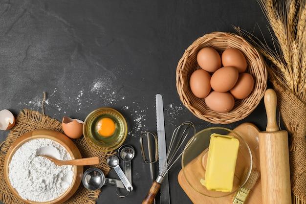Хлебная мука со свежим яйцом, несоленое масло и аксессуары для выпечки на деревянном фоне, подготовка к концепции домашней выпечки
