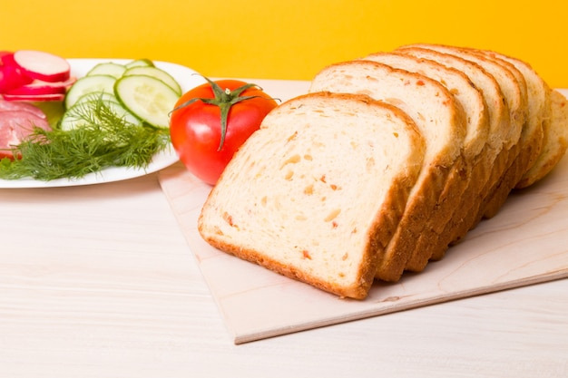 野菜のスライスとトーストのパンは木製のまな板の上にあります