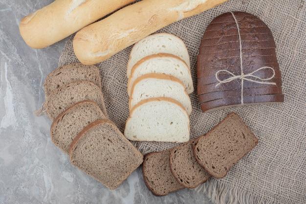 Varietà di alimenti freschi di pane su tela di sacco.