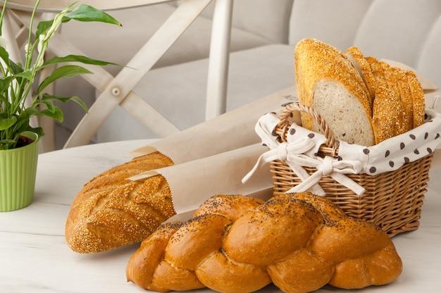 テーブルの明るい背景に籐のバスケットのパン