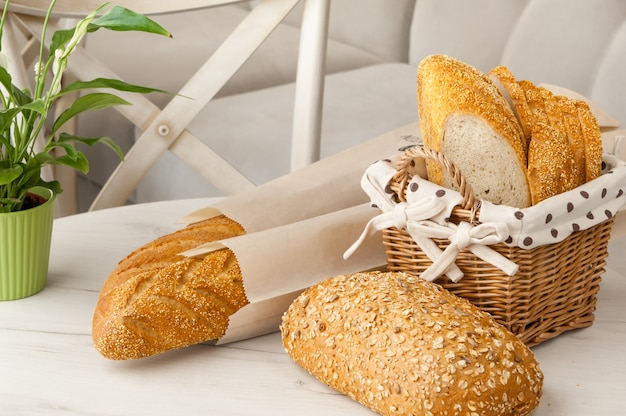 Хлеб в плетеной корзине на светлом фоне на столе