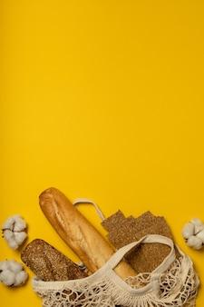 Хлеб в хлопковом экологически чистом пакете на желтой поверхности