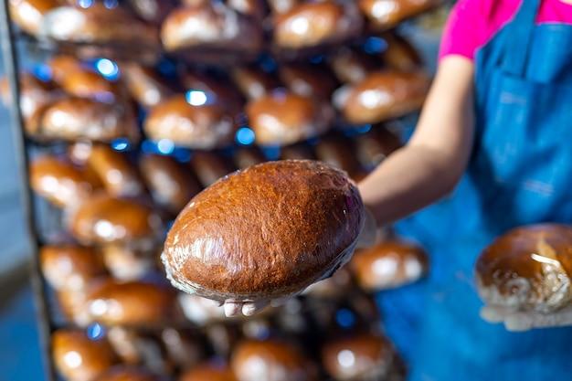 工業用オーブンの背景にパン屋の手でパン。工業用パンの生産